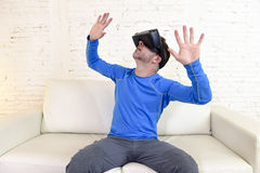 Happy man at home living room sofa couch excited using 3d goggles watching 360 virtual reality. Young modern man at home living room sofa couch excited using 3d Royalty Free Stock Images