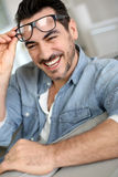 Happy man at home removing eyeglasses Stock Image