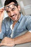 Happy man at home removing eyeglasses Stock Image