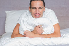 Happy man hugging his pillow Stock Photography