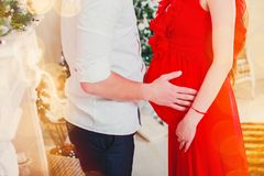 Happy man hugging his pregnant woman in the living room having, the light give a cozy atmosphere. Happy men hugging his pregnant women in the living room having royalty free stock image