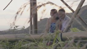 Happy man hugging young girl on green hills landscape covered tropical forest. Romantic couple embracing and enjoying.  stock footage