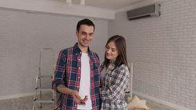 Portrait of a couple with a key in a new apartment. A happy man hugs his girlfriend in a new apartment among the boxes and tosses the key in his hand. Young stock video
