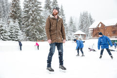 Happy man in ice skates looking away outdoors Royalty Free Stock Photo