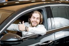 Free Happy Man In A New Car At The Showroom Royalty Free Stock Photo - 132859235