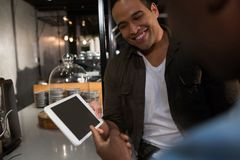Happy man interacting while using digital tablet royalty free stock photography
