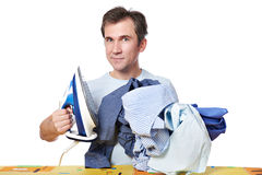 Happy man with iron and pile of crumpled shirts Stock Photography
