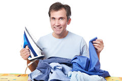 Happy man with iron and pile of crumpled shirts Royalty Free Stock Photos