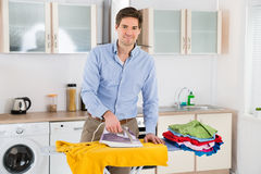 Happy Man Ironing Clothes Royalty Free Stock Photography