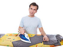 Happy man ironing his gray pants isolated. Housework Stock Image