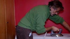 Happy man ironing stock footage