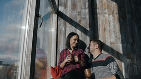 Happy man joyfully approaches his girlfriend and they together drink coffee near the big window. Slow motion stock video