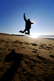 Happy man jumping. Photo of a man jumping on the beach Stock Photography