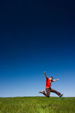 Happy man jumping. Active happy young man jumping in a green field against a clear blue sky royalty free stock images