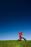 Happy man jumping. Active happy young man jumping in a green field against a clear blue sky stock photography
