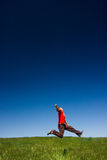 Happy man jumping. Active happy young man jumping in a green field against a clear blue sky stock photos