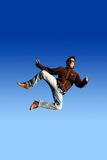 Happy man jumping. Isolated against a clean blue sky stock photos