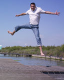 Happy man jumping. A outdoor portrait of a happy young man jumping on a pontoon Royalty Free Stock Photography
