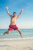 Happy man jumping on the beach Stock Photo