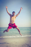 Happy man jumping on the beach Stock Photography