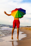 Happy man jumping on the beach with umbrella Stock Image