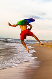 Happy man jumping on the beach with umbrella Royalty Free Stock Images