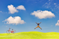 Happy man jumping on green grass field Stock Images
