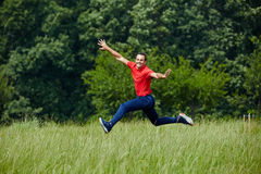 Happy man jumping for joy. Man jogging and jumping for joy by the forest Royalty Free Stock Images