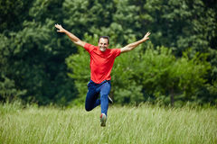 Happy man jumping for joy. Man jogging and jumping for joy by the forest Royalty Free Stock Photography