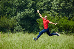 Happy man jumping for joy. Man jogging and jumping for joy by the forest Stock Photos