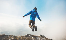 Happy Man jumping on mountains cliff to clouds sky Stock Photography