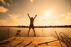 Happy man jumping on pier Royalty Free Stock Photography
