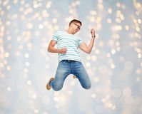Happy man jumping and playing imaginary guitar. Motion, fun and people concept - happy young man jumping in air and playing imaginary guitar over holidays lights Royalty Free Stock Images