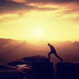 Happy man  jumping between rocks, misty mountains. Royalty Free Stock Image