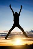 Happy Man jumping at Sunset Stock Image
