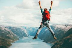 Happy Man jumping Travel Lifestyle adventure concept. Active summer vacations with backpack outdoor in Norway success and fun emotions above Lysefjord cliff stock photo