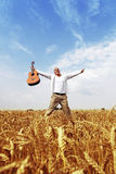 Happy man jumping in a wheat field Stock Photos