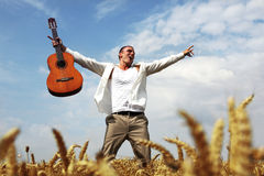 Happy man jumping in a wheat field. With his guitar Stock Photography