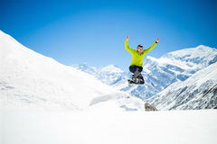 Happy man jumping in winter mountains Royalty Free Stock Photo