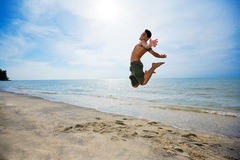 Happy man juumping. Happy man jumping up high by the beach in a beautiful day Stock Image