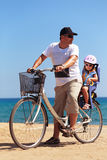 Happy man and kid girl biking on blue sea background Royalty Free Stock Images