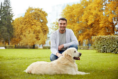Happy man with labrador dog in autumn city park Stock Images