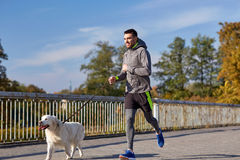 Happy man with labrador dog running outdoors. Fitness, sport, people, pets and lifestyle concept - happy man with labrador retriever dog running outdoors royalty free stock photos
