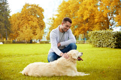 Happy man with labrador dog walking in city. Family, pet, animal and people concept - happy man with labrador retriever dog walking in autumn city park royalty free stock image