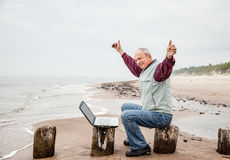 Happy man with a laptop on the beach Royalty Free Stock Photo