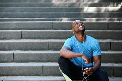 Happy man laughing with mobile phone and earphones Stock Image