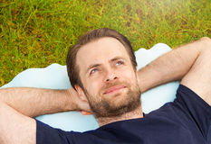 Happy man laying on grass and looking up Stock Images