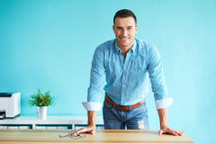 Happy man leaning on a table stock images