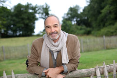 Happy man leaning on wood fence Royalty Free Stock Images