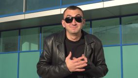 Happy man in leather jacket and sunglasses standing outdoor and laughing.  stock video footage